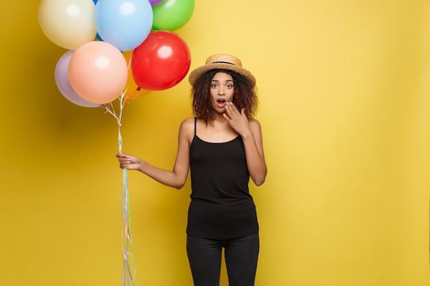 Celebration concept - close-up portret gelukkige jonge mooie afrikaanse vrouw in zwarte t-shirt lachend met kleurrijke party ballon. gele pastelstudio achtergrond.