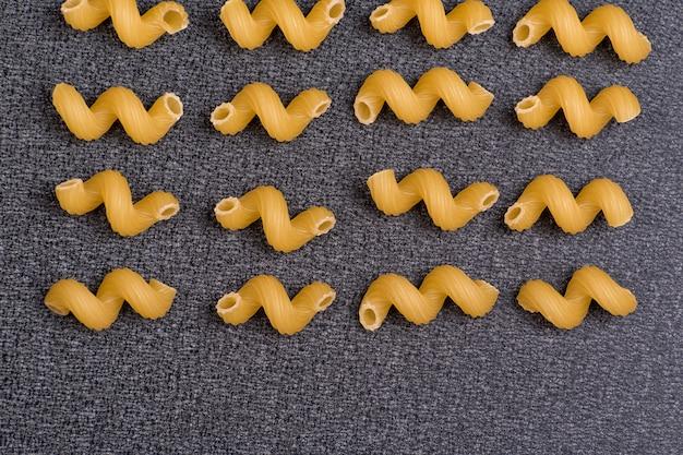 Cellentani op een grijze achtergrond. cavatappi close-up. italiaanse pasta achtergrond