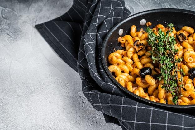 Cellentani puttanesca zeevruchten tonijn pasta in een pan. witte achtergrond. bovenaanzicht. ruimte kopiëren.