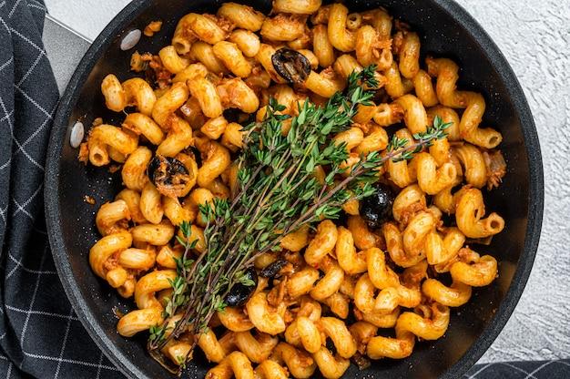 Cellentani puttanesca zeevruchten tonijn pasta in een pan. witte achtergrond. bovenaanzicht.