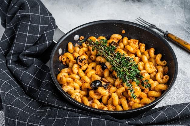 Cellentani puttanesca zeevruchten tonijn pasta in een pan