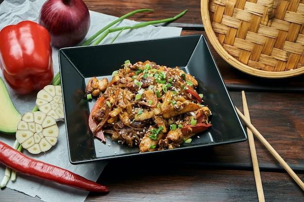 Cellofaannoedels met babymais, paprika, uien, wortelen en kip gebakken op een wok met teriyakisaus in zwarte plaat. lekker aziatisch straatvoedsel