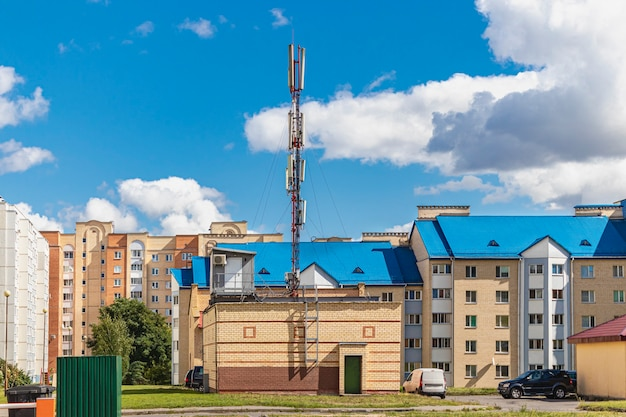 Cellulaire antenne tegen een blauwe bewolkte hemel in een woonwijk. moderne communicatietechnologieën.