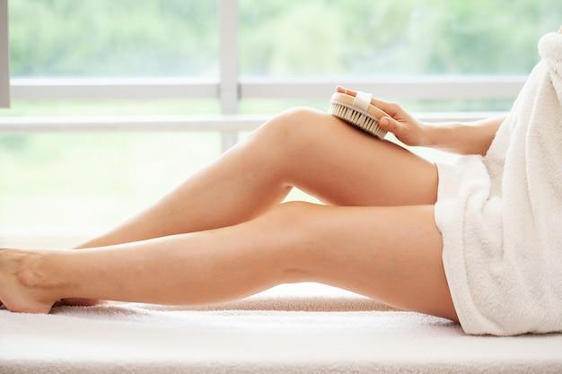 Cellulitisbehandeling, vrouwenarm die droge borstel tegen haar been houdt