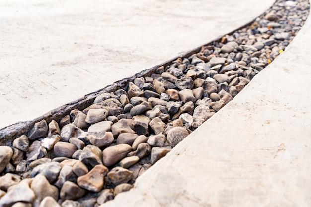 Cement doorkruist door een diagonale lijn van kiezelstenen steen