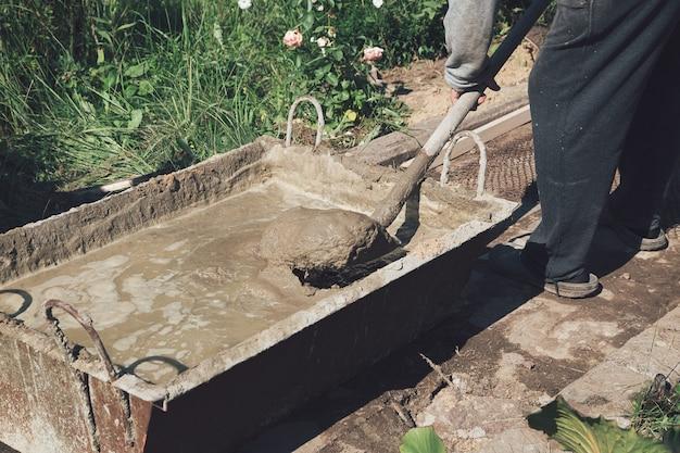 Cement mengen om het tuinpad te vullen, tuinbouwwerkzaamheden.