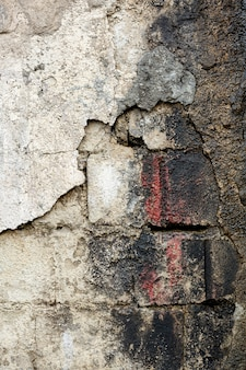 Cementmuur met blootgestelde vuile bakstenen en verf