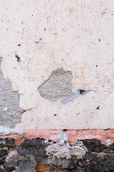 Cementmuur met vlekken en bakstenen