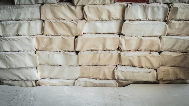 Cementzakken op een rij op huis in aanbouw.