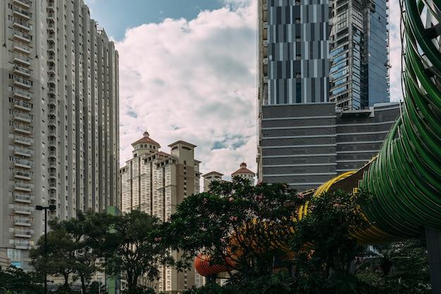 Centraal jakarta stadsgezicht met hoogbouw, wolkenkrabbers en hotel in toeristisch gebied met groene bomen.