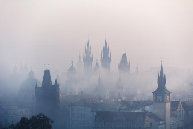 Centrum van praag en de karelsbrug in de mist in de vroege ochtend met torens en silhouetten