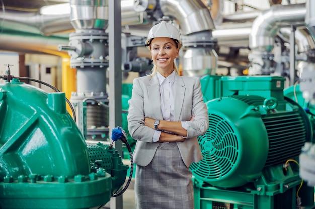 Ceo in pak met helm op hoofd staande in verwarmingscentrale met gekruiste armen