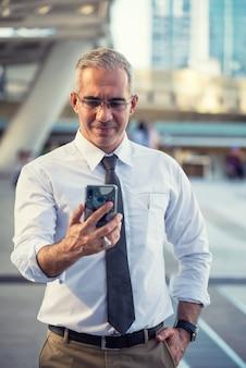 Ceo zakenman op slimme telefoon in stad
