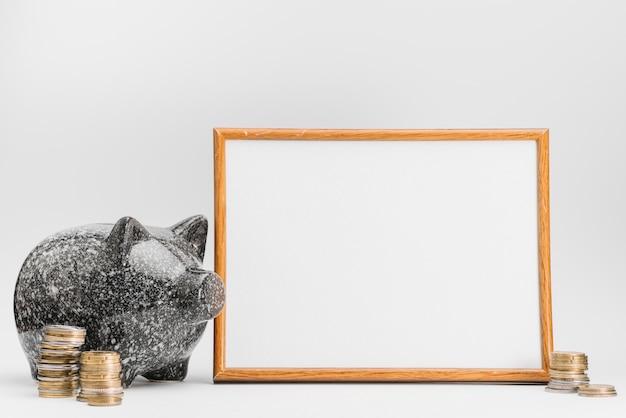 Ceramische piggybank met stapel muntstukken dichtbij de witte raad tegen witte achtergrond