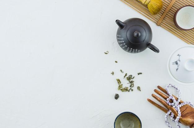Ceramische theepot en koppen met kruiden die op witte achtergrond worden geïsoleerd