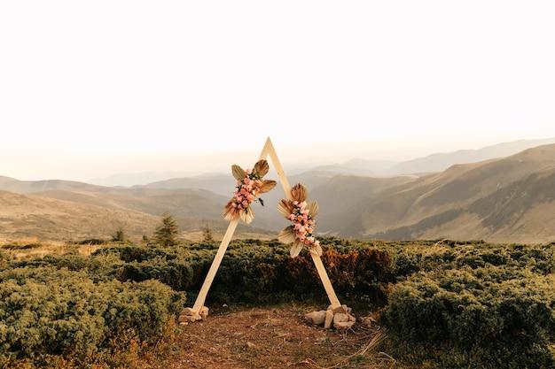 Ceremonie, boog, huwelijksboog, huwelijk, huwelijksmoment, decoraties, decor, huwelijksdecoraties, bloemen, buitenceremonie in de open lucht, boeketten bloemen.