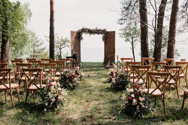 Ceremonie, boog, huwelijksboog, huwelijk, huwelijksmoment, decoraties, decor, huwelijksdecoraties, bloemen, stoelen, buitenceremonie in de open lucht, boeketten bloemen.
