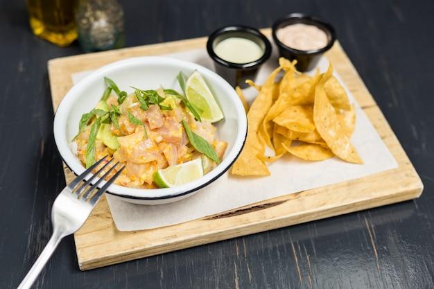 Ceviche met sauzen en frietjes op een houten tafel