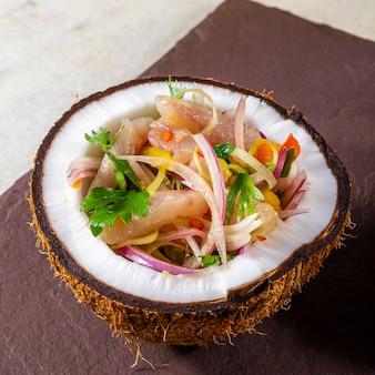 Cevicheschotel - voorgerecht van verse vis gemarineerd in citrus met tropisch fruit geserveerd in een coconut bowls.