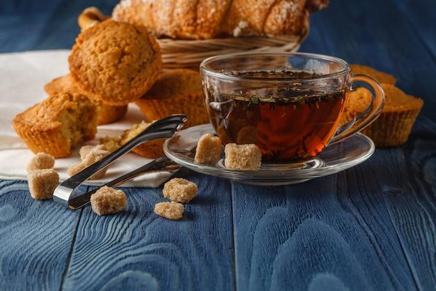 Ceylon zwarte thee in glazen bekers, verse croissants, vintage houten tafel