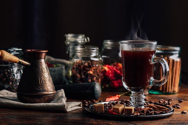 Cezve en glas koffie met bonen sugar star anise kaneelstokje en chilipeper op dienblad