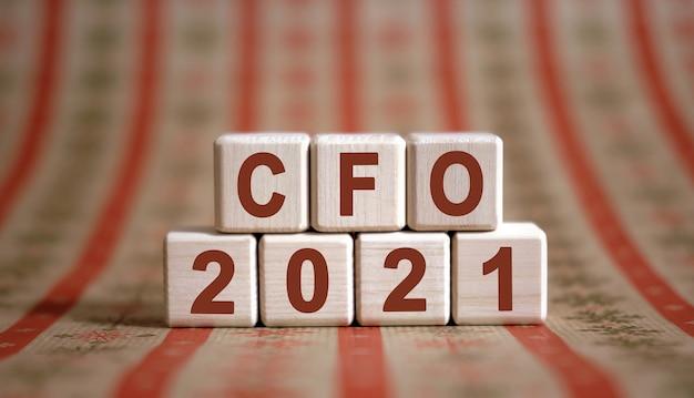Cfo 2021 tekst op houten kubussen op een monochrome achtergrond met reflectie.