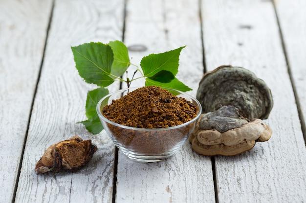 Chaga berk paddestoel met berken bladeren op een lichte tafel. berkenchampignons in korrels. fytotherapie. biologische superfood. landelijke stijl