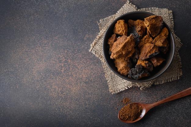 Chaga-berkpaddestoelen in kom op zwarte lijst. trendy gezonde superfood voor infusie, thee of koffie. kopieer ruimte.