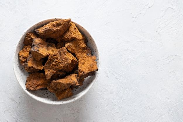 Chaga birch mushrooms in kom op lichte lijst. trendy gezonde superfood voor infusie, thee of koffie. kopieer ruimte.