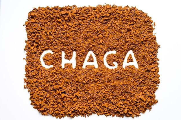 Chaga-paddenstoel. handgeschreven tekst chaga in een stapel van kleine fragmenten van berk schimmel chaga op wit