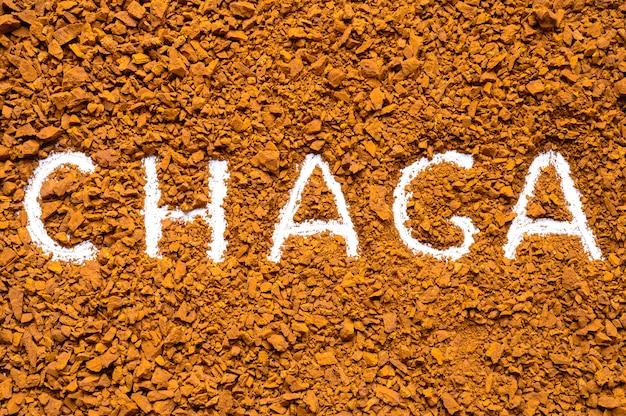 Chaga-paddenstoel. handgeschreven tekst chaga op een achtergrond van een stapel kleine fragmenten van berkenschimmel chaga