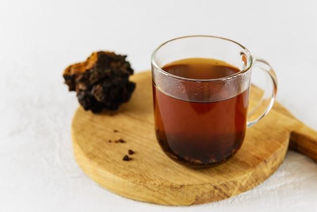 Chaga paddestoel thee in een glazen mok op een houten bord