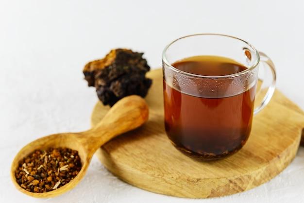 Chaga-thee in een glazen mok met een lepel op een houten bord