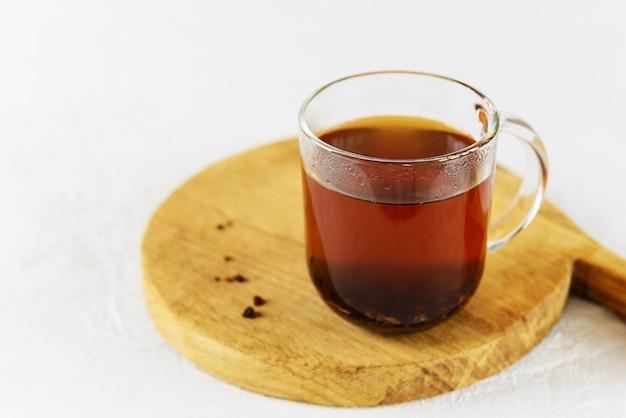 Chaga thee in een glazen mok op een houten bord