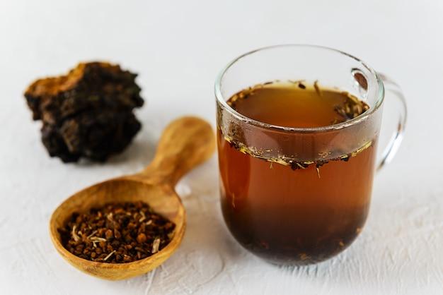Chaga-thee in een glazen mok op een lichte achtergrond