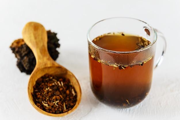 Chaga thee in een kopje op een lichte tafel