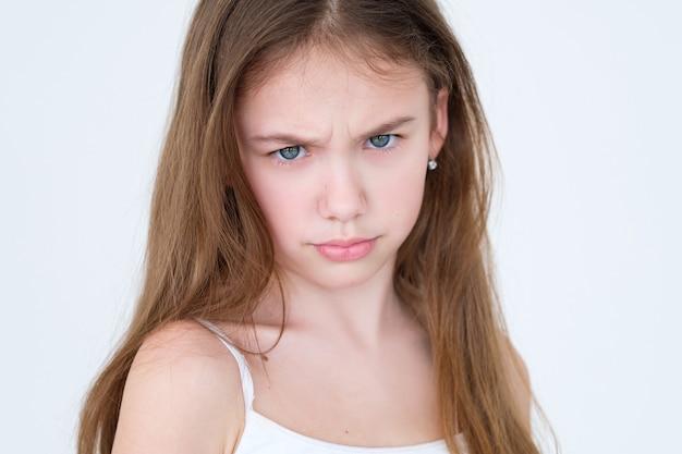 Chagrijnig ontevreden kind fronsen op witte muur.