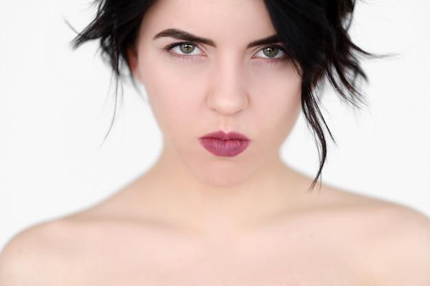 Chagrijnige beledigde vrouw met samengeknepen lippen en doordringende blik op witte muur.