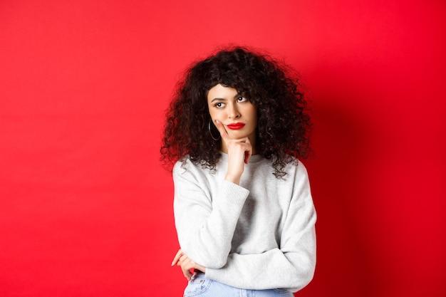 Chagrijnige jonge vrouw met krullend haar, die geïrriteerd of verveeld kijkt naar lege ruimte, peinzend en verdrietig op rode muur staat