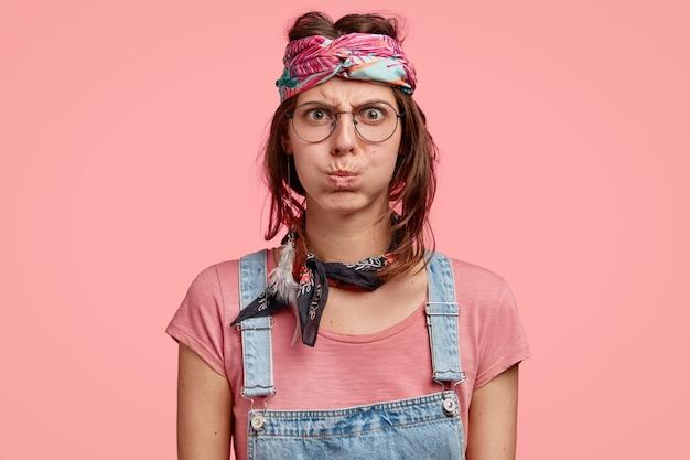 Chagrijnige nors hippievrouw blaast met onverschilligheid, heeft een boze gezichtsuitdrukking