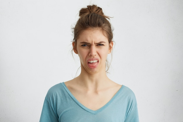 Chagrijnige vrouw toont haar walging terwijl fronsen gezicht met ontevredenheid met haar tong.