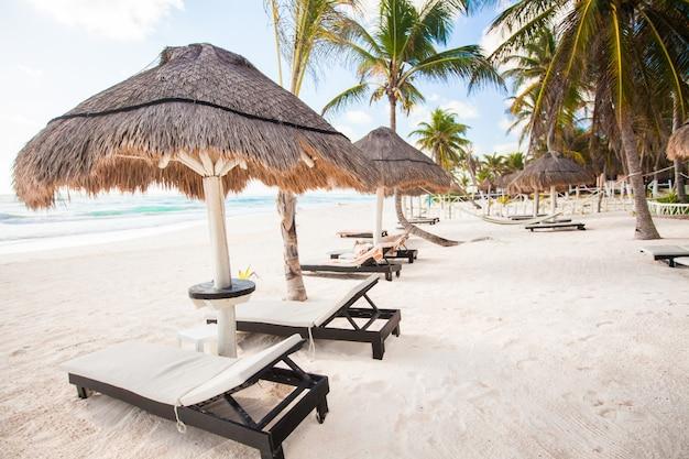 Chaise lounges onder een paraplu op het zandstrand