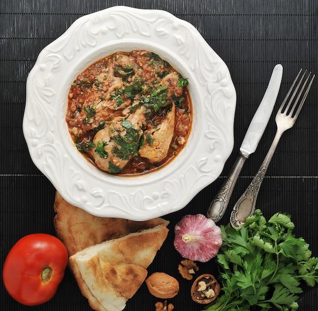 Chakhokhbili - traditioneel georgisch gerecht, kip gestoofd met kruiden en tomaten