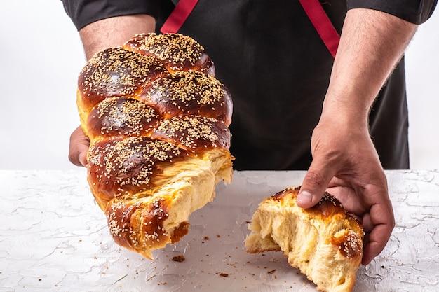 Challah joods brood in handen van de mens, zelfgemaakt bakken, traditioneel joods brood, joodse gebakjes