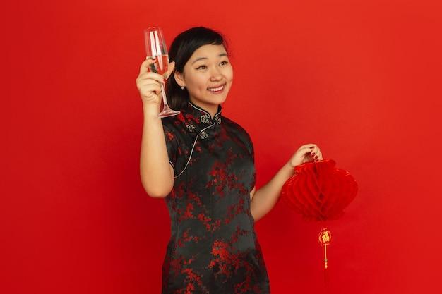 Champagne drinken en lantaarn vasthouden. gelukkig chinees nieuwjaar. aziatisch jong meisje portret op rode achtergrond. vrouwelijk model in traditionele kleding ziet er gelukkig uit. copyspace.