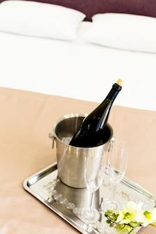 Champagne-emmer dichtbij bed in een hotelkamer