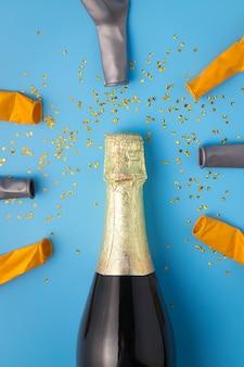 Champagne-fles en ballon op blauwe achtergrond.