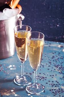 Champagne-fles in emmer met ijs en glazen champagne