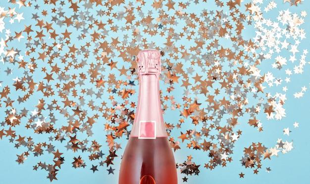 Champagne-fles met confettien op blauwe achtergrond