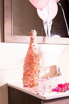 Champagne-fles met een oranje en witte confettien op bureau wordt behandeld dat